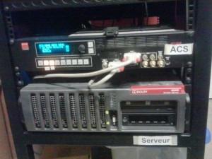 """Serveur Dolby DSS200 avec un """"switch vidéo"""" au-dessus."""